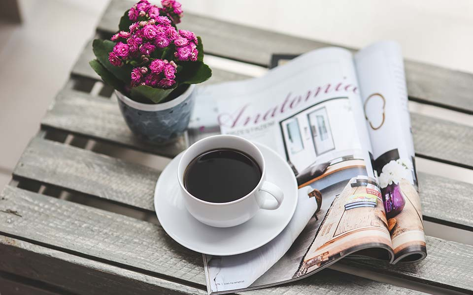 A cup of coffee holds down a newspaper next to a small pot of roses.