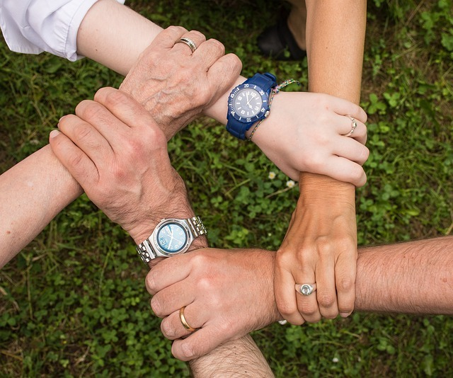 Five people huddling and holding each other's wrists.