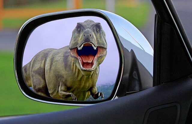 Dinosaur approaching and seen in rearview mirror.