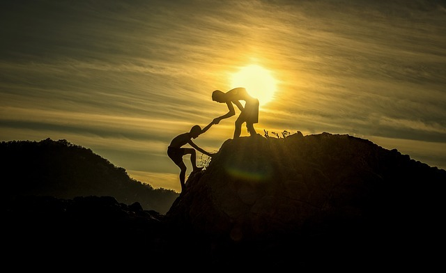 One person helping another up a mountain at sunset.