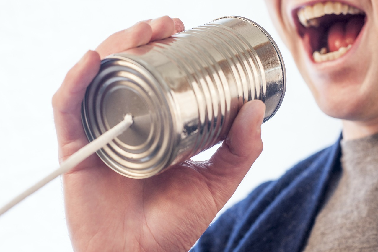 Man shouting into a tin phone can.
