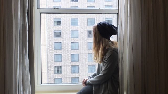 Woman with a beanie sits in the window sill