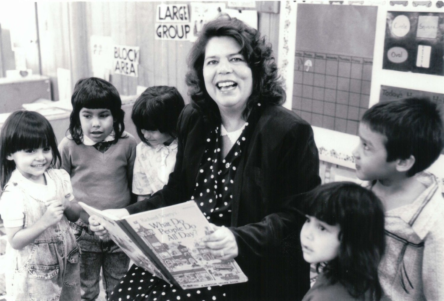 Black and white photo fo Wilma Mankiller surrounded by school children
