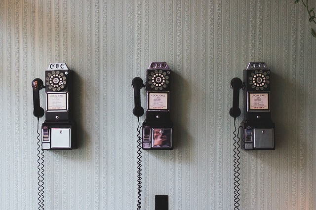 Three vintage phones hanging on a striped wall