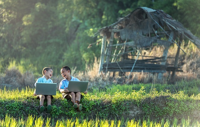 Two kids laughing while typing on laptops in a field