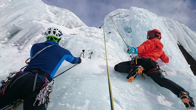 Two people ice climbing and helping each other