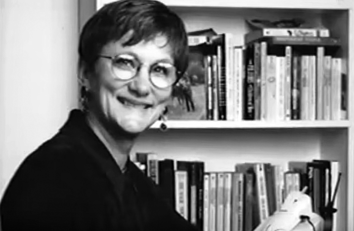 Black and white photo of Anita Borg in front of a bookcase