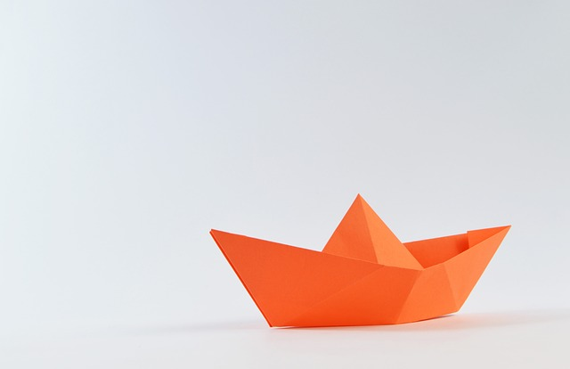 Orange paper boat against a white background