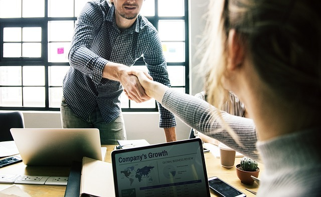 Two co-workers shaking hands in a loft office