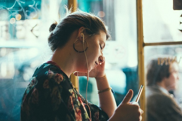 Woman in front of window looking at phone