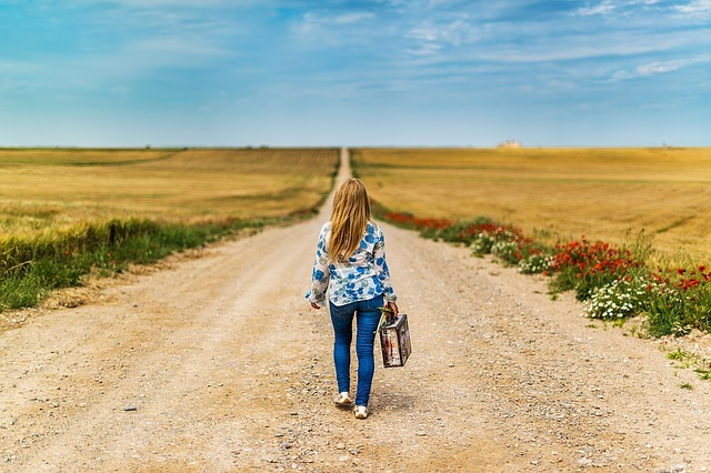Woman with a suitcase facing a wide open road