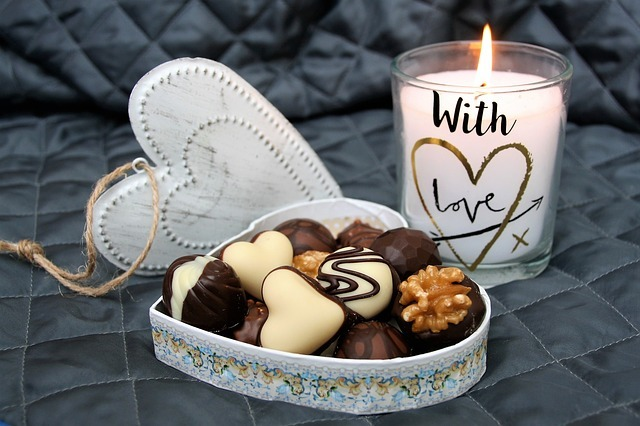 Candle next to a box of chocolates
