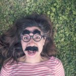 Woman lying on grass wearing a Groucho Marx mask