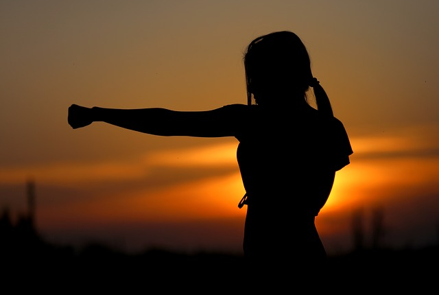 Woman practices karate at sunset